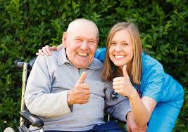 Man in Wheelchair and Carer smiling and giving the thumbs up sign