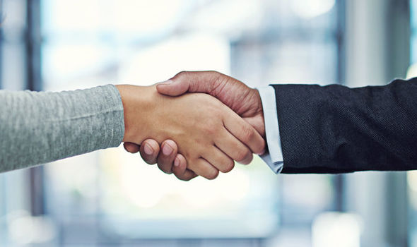 The hands of two individuals joined together in a handshake representing partnership working