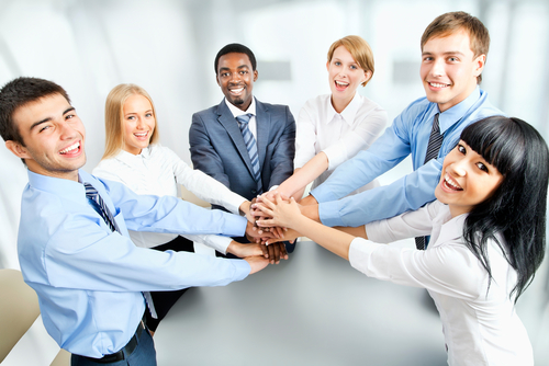 Group of professionals holding hands representing partnership working