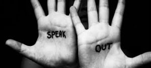 Two hands with the words 'Speak Out' written on the palms