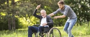 Carer pushing a client in a wheelchair. Both look really happy.