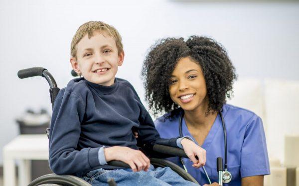 A boy in a wheelchair with a nurse