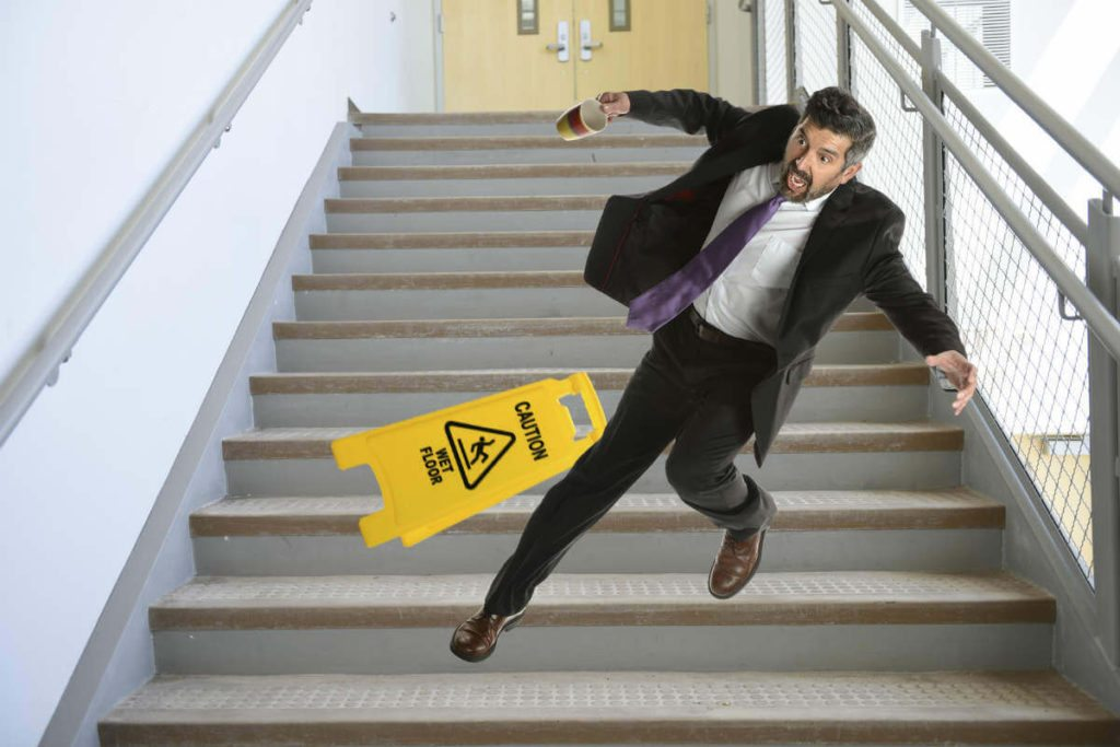 Accident represented by a man falling down the stairs. A slippery floor sign is also visible.