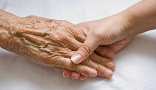 A older person's hand holding a younger person's hand