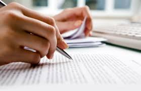 The hands of a care worker completing paperwork. With one hand they flick through a pile of paper records and with the other they are writing
