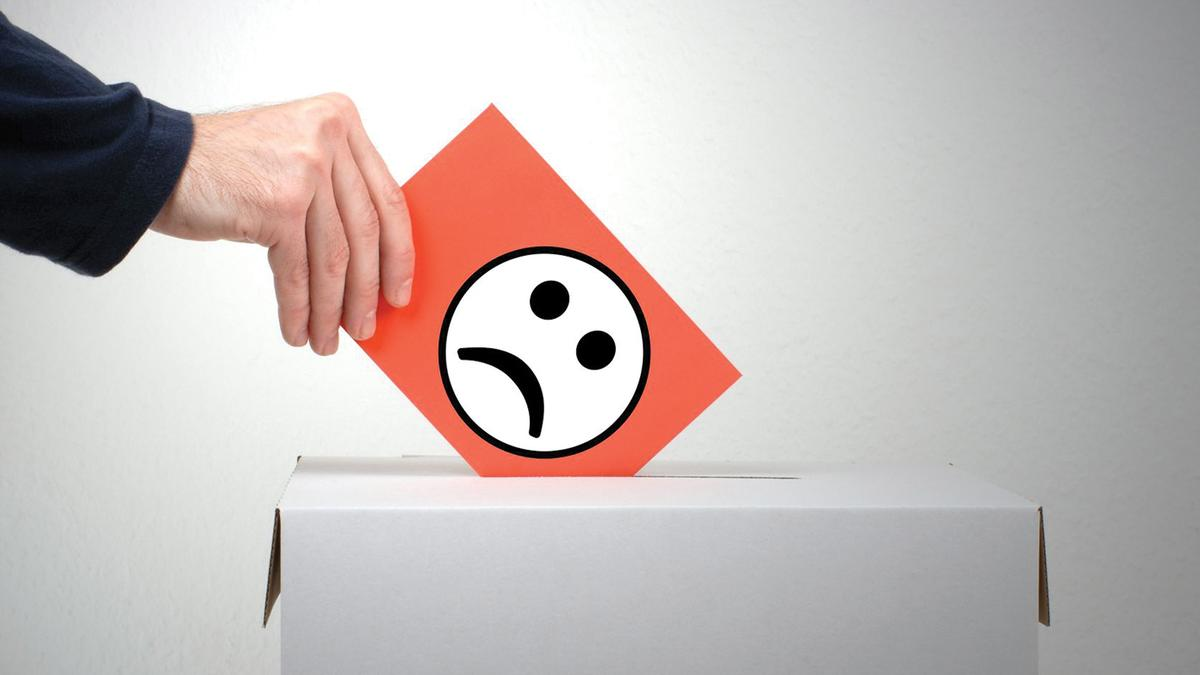 An hand posting a card with a picture of a sad face on it into a box representing making a complaint