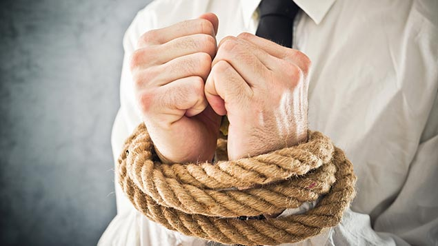 A man's wrists bound together by a length of rope representing restrictive practice